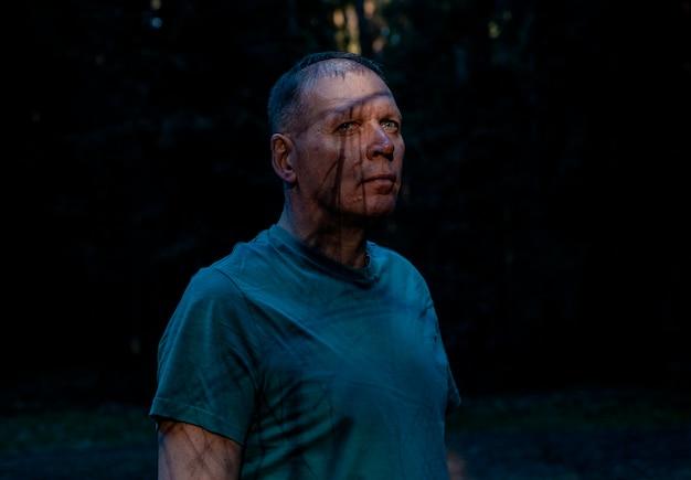 Portrait d'homme effrayant avec une ombre sur le visage dans une forêt sombre, regard effrayant d'un homme âgé mature, folie horro...