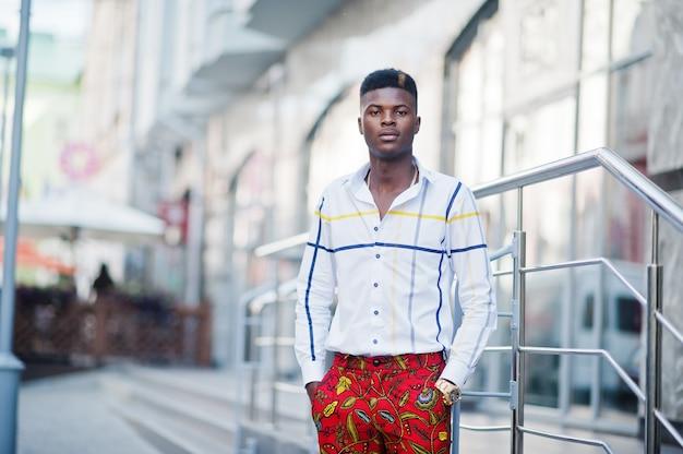 Portrait de l'homme élégant beau modèle afro-américain en pantalon rouge et chemise blanche.