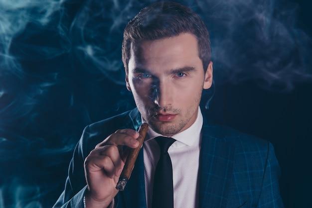 Portrait d'un homme élégant en fumée tenant un cigare
