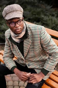 Portrait d'homme élégant posant sur un banc