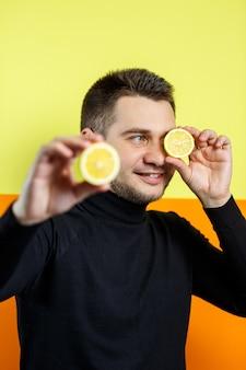 Portrait d'un homme élégant en raglan noir avec un citron tranché dans les mains. mec élégant. un sourire sur son visage