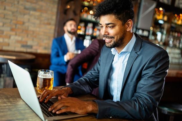 Portrait d'un homme entrepreneur prospère assis au café travaillant sur un ordinateur portable.