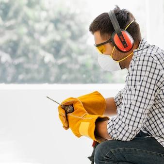 Portrait homme avec équipement de protection de sécurité avec perceuse