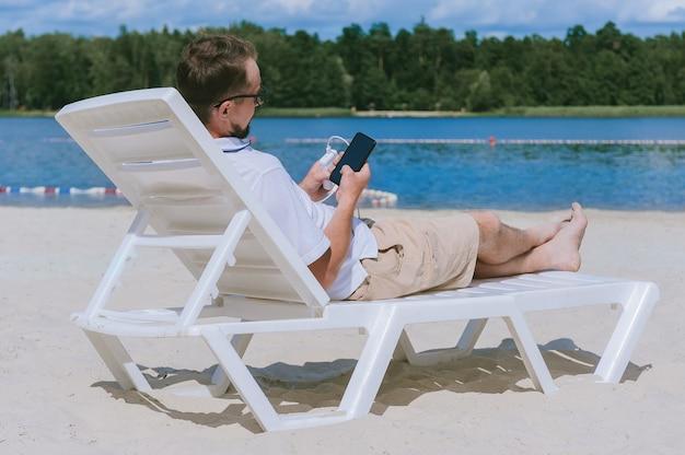 Un portrait d'un homme est allongé sur une chaise longue et charge un smartphone à partir d'une banque d'alimentation sur la plage. sur fond de sable, d'eau et de forêt.