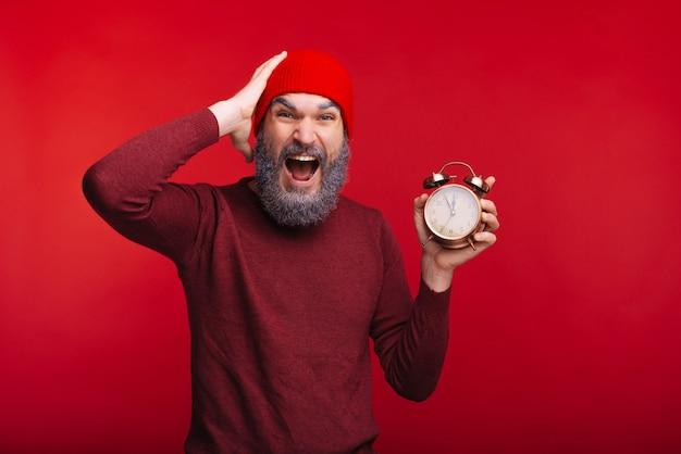 Portrait d'un homme étonné avec barbe blanche tenant un réveil