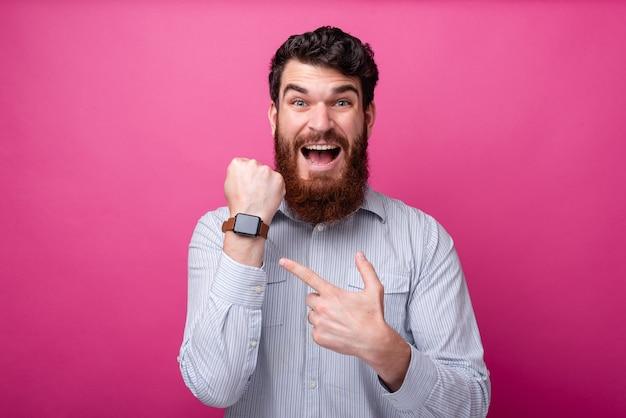 Portrait d'un homme étonné pointant sur sa montre intelligente