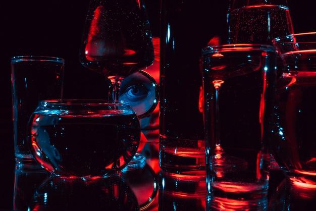 Portrait d'un homme étrange regardant à travers une loupe et des verres avec de l'eau avec des lumières rouges