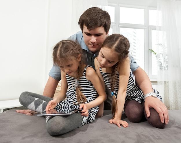 Portrait d'homme étreignant deux jeunes filles regardant la tablette