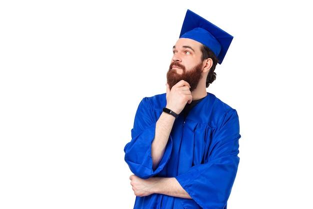 Portrait d'homme étudiant barbu vêtu d'une robe bleue et de la pensée