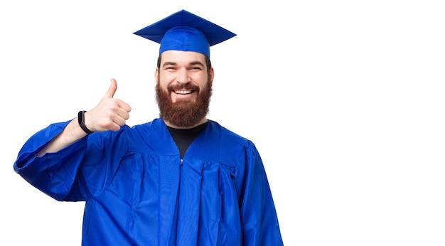 Portrait d'homme étudiant gai avec barbe portant baccalauréat montrant le pouce vers le haut