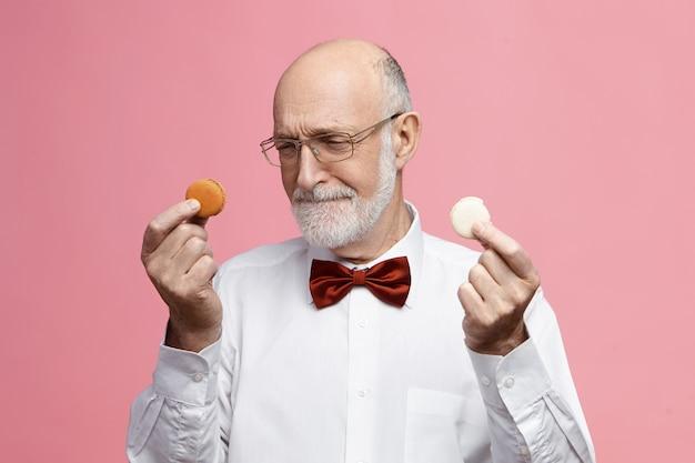 Portrait d'un homme européen âgé et élégant avec une barbe épaisse tenant deux minuscules macarons à deux mains, en les regardant, en décidant lequel des biscuits manger en premier, ayant une expression faciale confuse douteuse