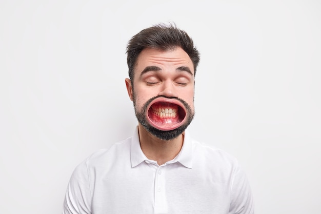Portrait d'un homme européen non rasé garde les yeux fermés ouvre la bouche serre les dents vêtu d'une chemise décontractée