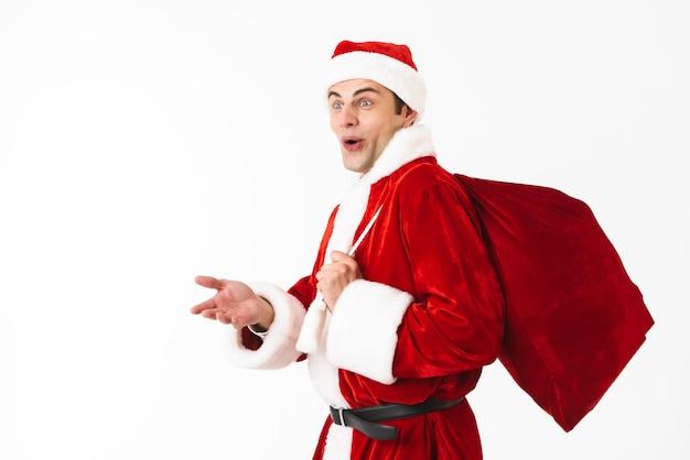 Portrait d'homme excité des années 30 en costume de père noël et chapeau rouge marchant avec sac-cadeau sur l'épaule