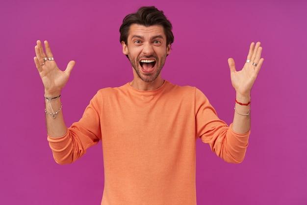 Portrait d'homme excité aux cheveux et soies brune. porter un pull orange à manches retroussées. a des bracelets et des bagues. lève les mains