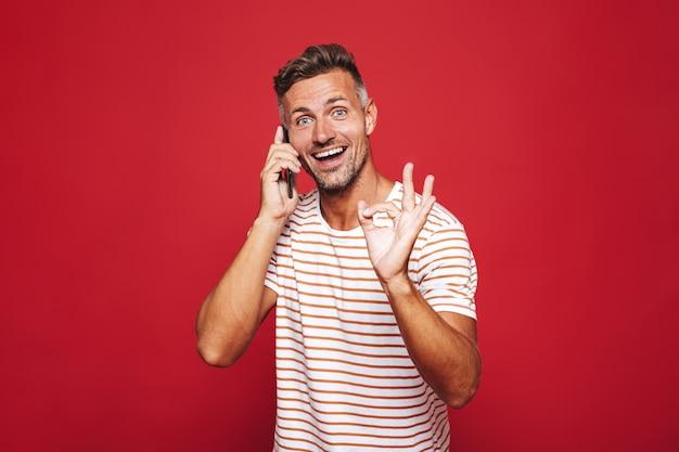 Portrait d'un homme excité debout sur le rouge