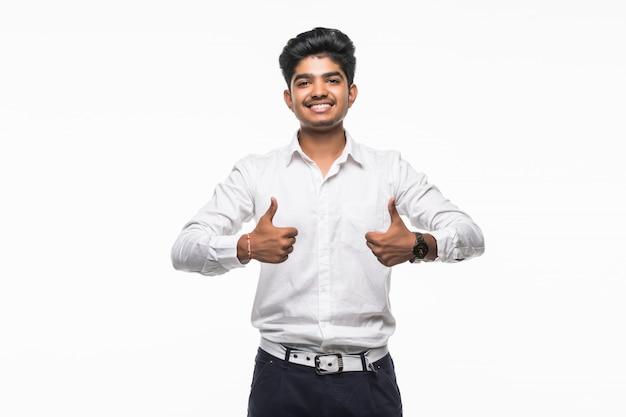 Portrait d'un homme excité en tenue de soirée donnant le pouce contre le mur blanc