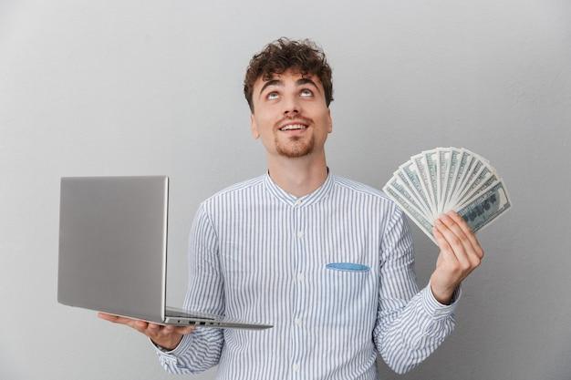 Portrait d'un homme excité vêtu d'une chemise souriant tout en tenant un ordinateur portable en argent et un tas d'argent en espèces isolé sur un mur gris
