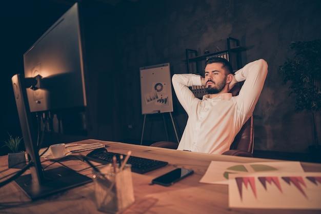Portrait d'homme fatigué sérieux s'asseoir sur une chaise regarder ordinateur à écran