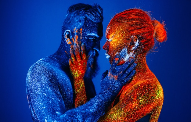 Portrait d'un homme et d'une femme barbus peints dans une poudre ultraviolette.