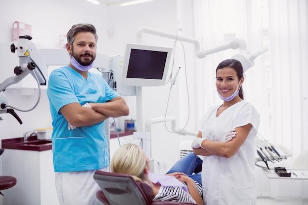 Portrait, de, homme femme, dentiste, debout, dans, clinique dentaire