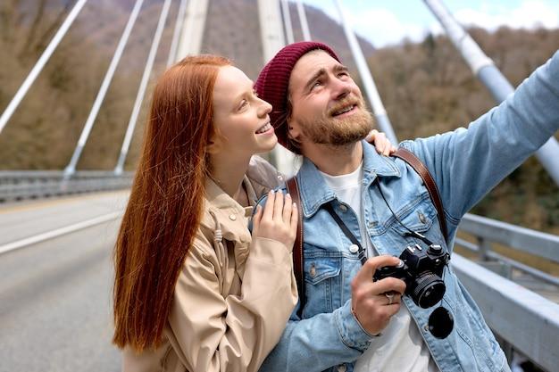 Portrait d'un homme et d'une femme de race blanche en tenue décontractée marchant sur le pont, en contemplant les montagnes, les paysages autour. beau mâle pointant le doigt sur le côté, montrant quelque chose à sa petite amie