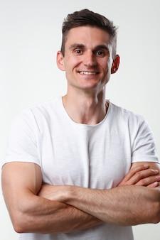 Portrait d'homme fitness mignon dans un réservoir blanc