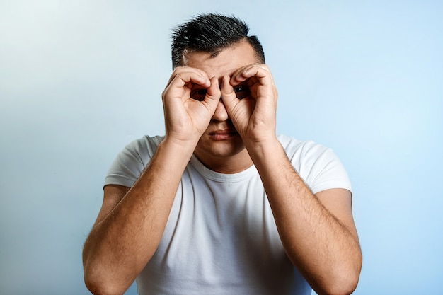 Portrait d'un homme sur un fond clair, fabrique des jumelles avec les mains, clairvoyant.