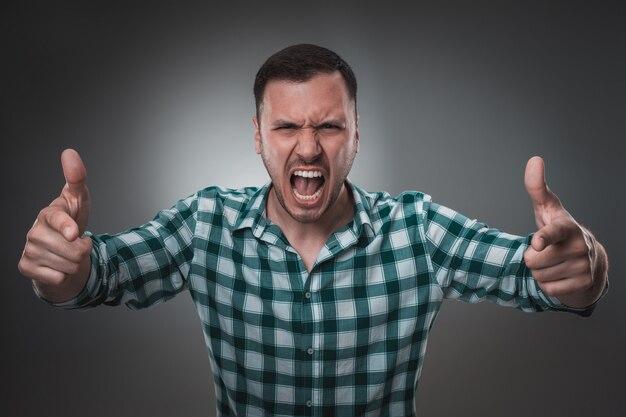Portrait d'homme sur fond gris. homme montrant différentes émotions.