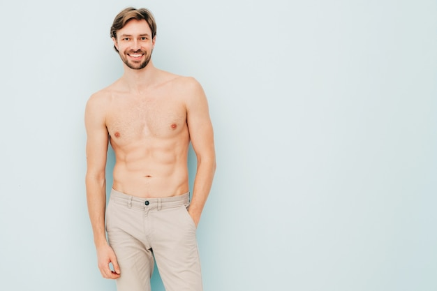 Portrait d'un homme fort beau sportif. modèle de remise en forme athlétique souriant et sain posant près du mur bleu clair