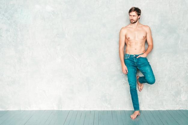 Portrait d'un homme fort beau sportif. modèle de remise en forme athlétique souriant et sain posant près d'un mur gris en jeans.