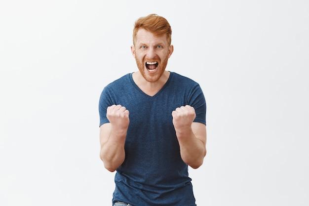 Portrait d'un homme fort rousse barbu mature en colère et énervé, serrant les poings près de la poitrine, criant de colère et fronçant les sourcils, voulant coup de poing