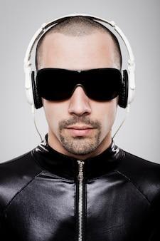 Portrait d'homme futuriste écoutant de la musique avec des écouteurs sur fond blanc