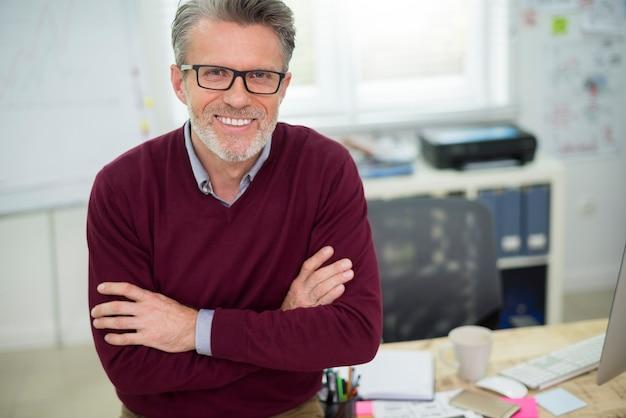 Portrait d'homme gai assis sur le bureau