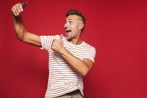 Portrait d'un homme gai debout sur le rouge