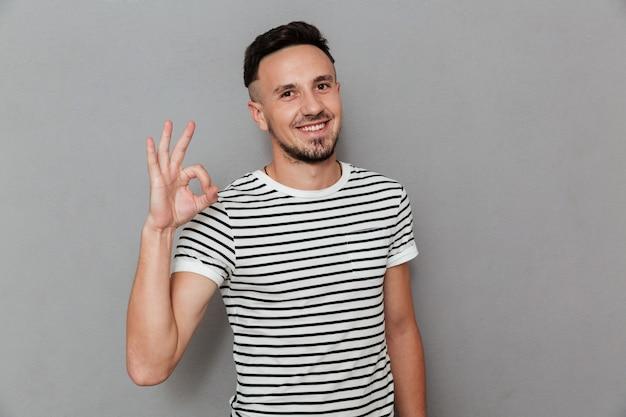 Portrait d'un homme gai heureux montrant le geste ok