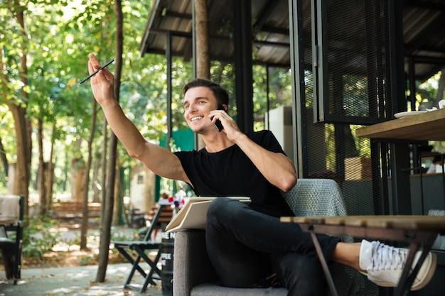 Portrait d'un homme gai heureux parler sur téléphone mobile