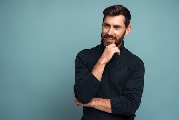 Portrait d'un homme gai et mal rasé, debout, la main près de son visage et souriant tout en détournant les yeux. concept d'apparence masculine. studio intérieur tourné isolé sur bleu