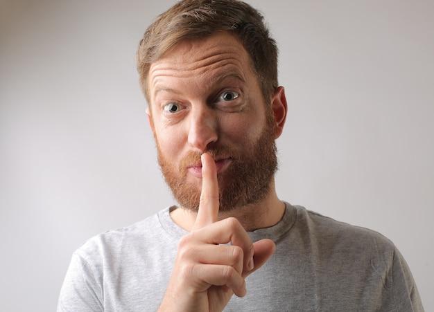 Portrait d'un homme gardant son doigt sur ses lèvres