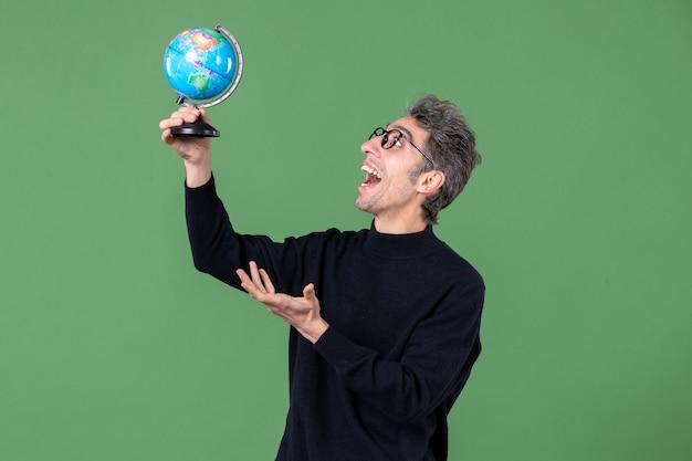 Portrait d'un homme de génie tenant un globe terrestre tourné en studio fond vert mer nature professeur air planète espace