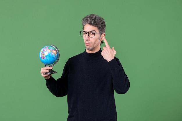 Portrait d'homme de génie tenant un globe terrestre tourné en studio fond vert professeur d'espace nature air mer