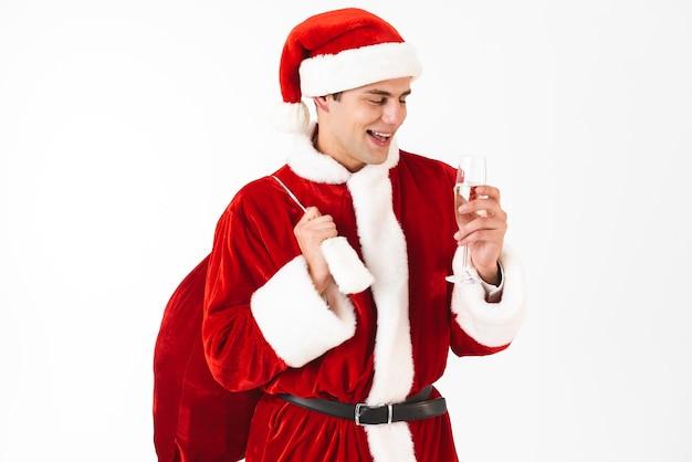 Portrait d'homme gentil des années 30 en costume de père noël et chapeau rouge tenant un sac-cadeau et un verre de champagne
