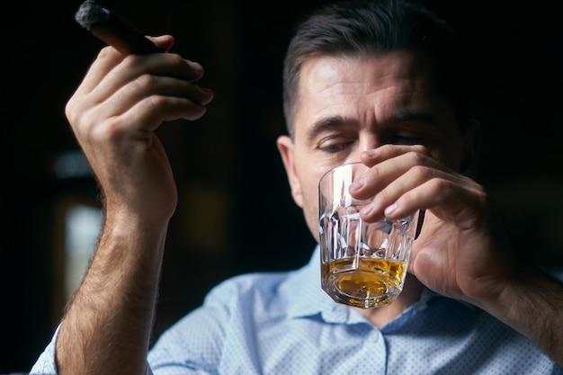 Portrait d'un homme hansome fumant un cigare dans un bar-salon et buvant du whisky