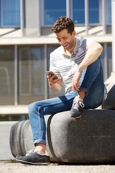Portrait d'un homme heureux assis à l'extérieur et à l'aide de téléphone portable