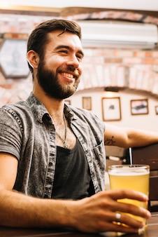 Portrait d'un homme heureux, boire de la bière au bar