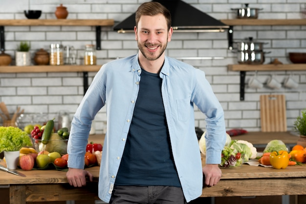 Portrait d'un homme heureux, debout dans la cuisine