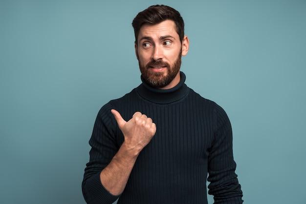 Portrait d'un homme heureux et excité avec une barbe pointant le côté avec son doigt, trouvez une solution ou une idée, obtenez une réponse à la question, eurêka. studio intérieur tourné isolé sur fond bleu