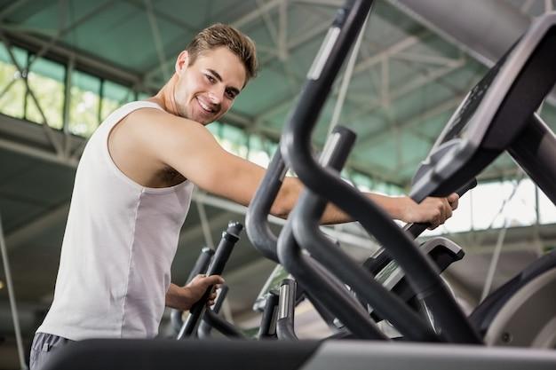 Portrait d'homme heureux exerçant sur la machine elliptique