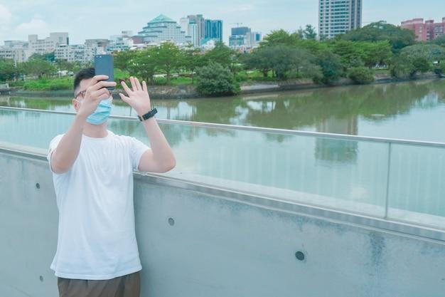 Portrait d'un homme heureux faisant des appels vidéo et dit bonjour avec son ami porte un masque