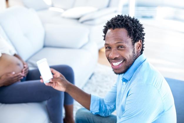 Portrait d'un homme heureux maintenant smartphone