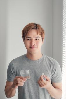 Portrait d'un homme heureux prenant la pilule de vitamine omega3